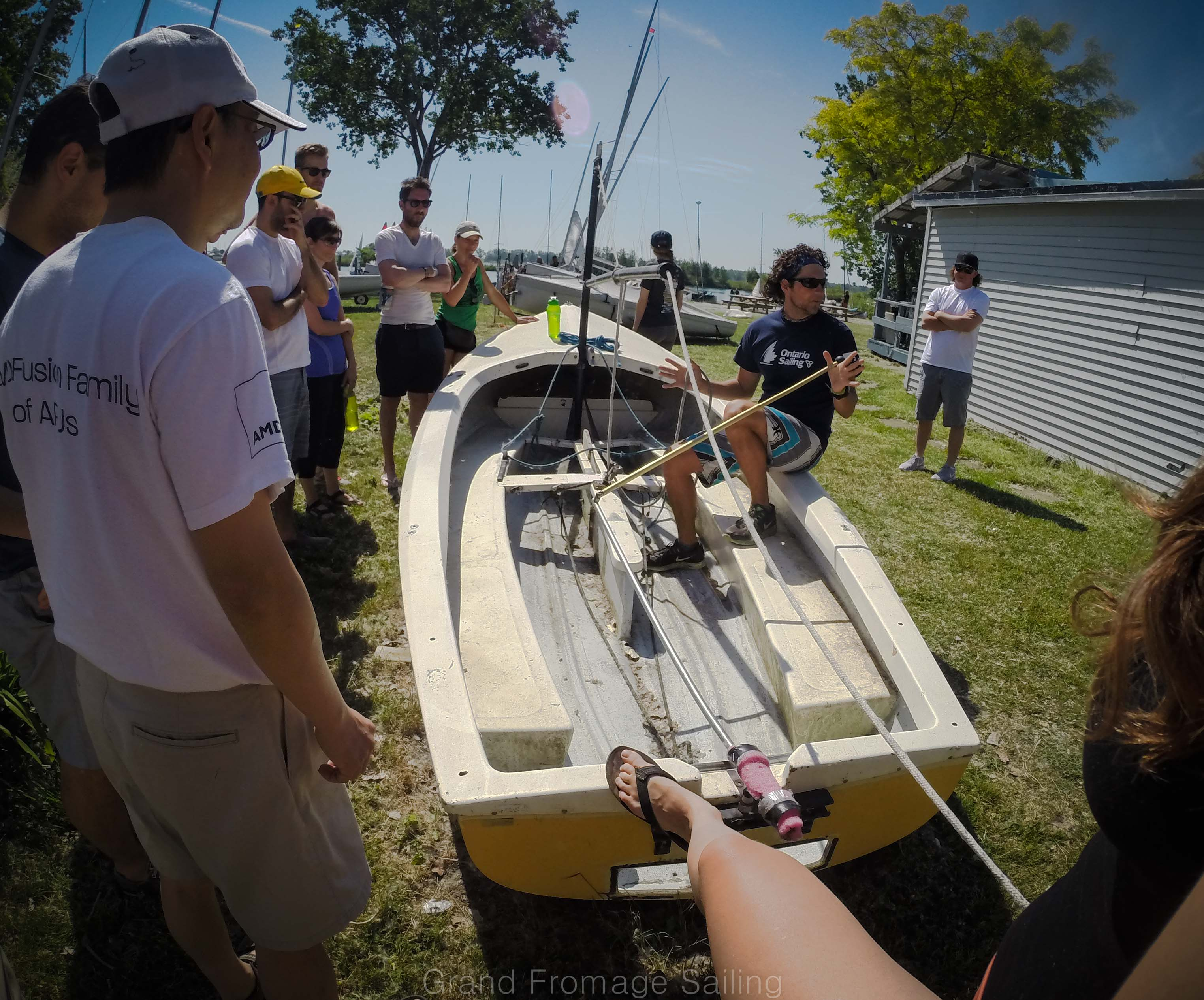 Alex Byczko demonstrating the tiller main sheet exchange on a land boat with athletes watching